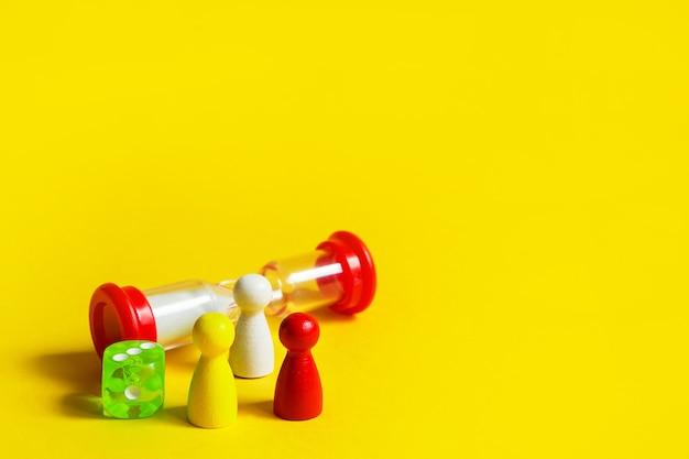 Lay-out van bordspellen op een gele achtergrond dobbelstenen, chips, zandloper timer.