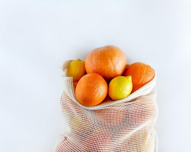 Lay-out van citrus in eco meshing bag, geïsoleerd. milieuvriendelijk. stop met plastic