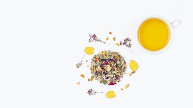 Lay-out van kopje groene thee met assortiment van verschillende droge theebladeren en bloemblaadjes op een witte achtergrond