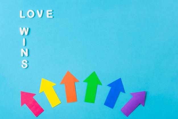 Lay-out van papieren pijlen in lgbt-kleuren en liefde wint woorden