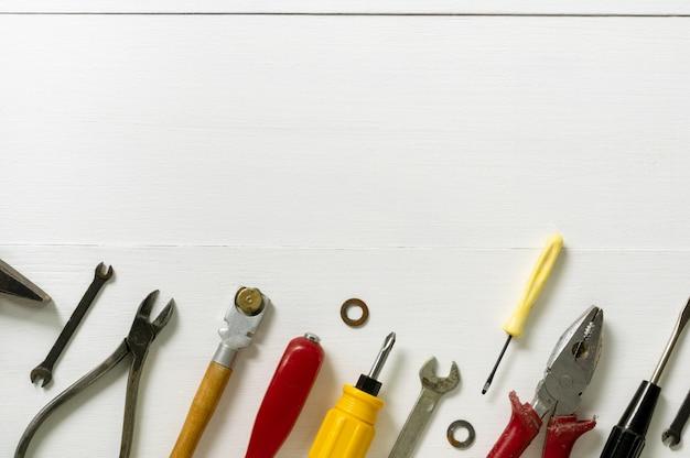 Lay-out van reparatie en bouwhulpmiddelen op een witte houten achtergrond. ruimte voor tekst