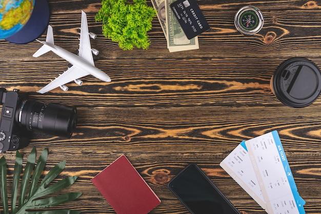 Lay-out van vliegtuig reisaccessoires op een houten achtergrond met kopie ruimte