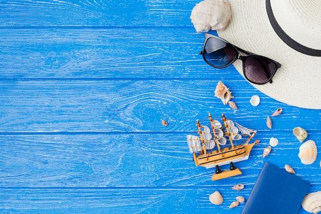 Lay-out van zeeschelpen dichtbij stuk speelgoed schip en zonnebril met hoed