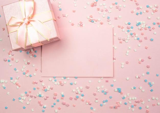 Lay-out voor opname. roze blad om te schrijven en een geschenkdoos op een roze achtergrond met decoratieve veelkleurige elementen met sterren en strikken. plat lag, bovenaanzicht
