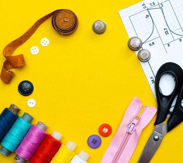 Layout naaien. handwerk, handwerk, naaien en maatwerk concept - doos met draadklosjes en knopen op tafel. het concept van naai-accessoires. plat liggen,
