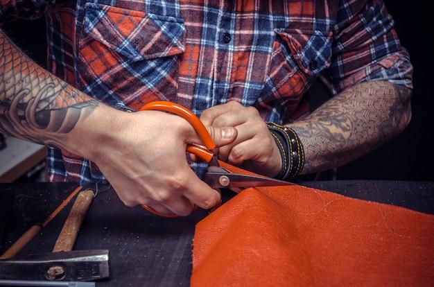 Leather artisan die lederwaren uitsnijdt in zijn leeratelier