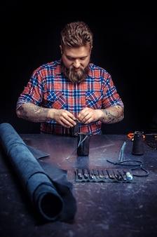 Leather artisan vervaardigt in een werkplaats een nieuw product van leer.