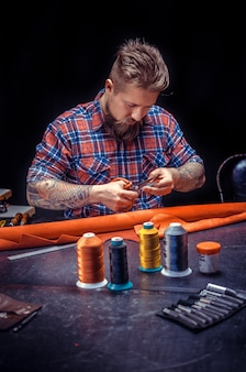Leather professional maakt kwaliteitsproduct van leer./leermeester aan het werk aan zijn nieuwe leerproduct in zijn winkel.