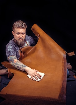 Leather workman creëert een nieuw leerproduct bij leather shop./leather professional werkt met leer.