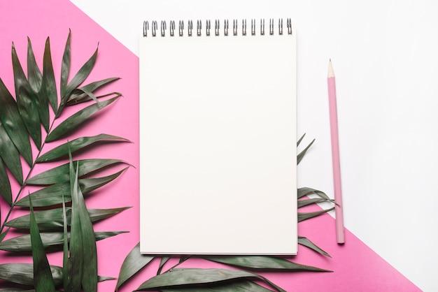 Leaves; lege spiraal blocnote en potlood op dubbele achtergrond