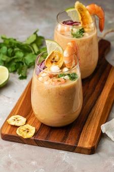 Leche de tigre, peruaans, ecuador, latijns-amerikaans eten, ceviche van rauwe viscocktail met limoen, aji limon en koriander. traditioneel peruaans eten met garnalen en bananenchips