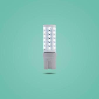 Led spaarlamp 230v in een keramische socket geïsoleerd op groene pastelkleurige achtergrond.