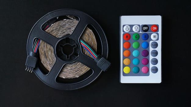 Led strip spoel close-up. diode met bedieningspaneel voor het wisselen van kleuren op donkere achtergrond.