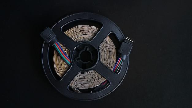 Led-tape spoel. led-verlichting tape op zwarte achtergrond. rgb-licht uit