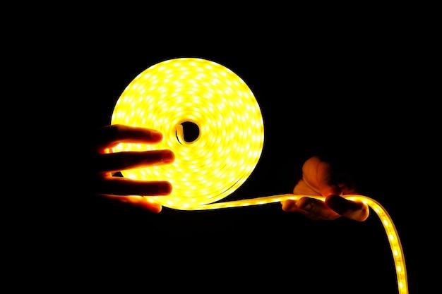 Led verlichting logo, led strip in handen in het donker.