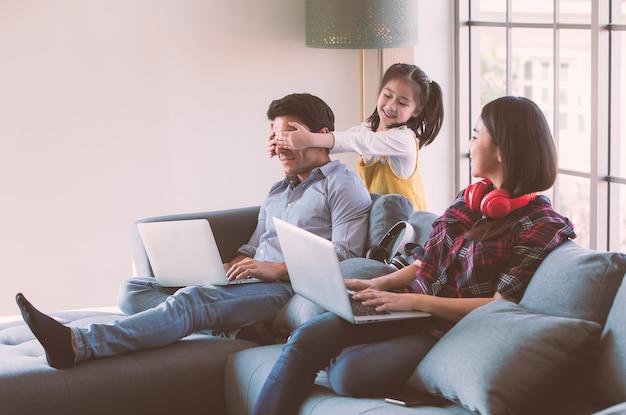 Leden van een diverse familie, een blanke vader en een aziatische moeder die een laptopcomputer gebruiken om thuis te werken, een jonge, schattige dochter van een klein meisje maakt een grapje met haar vader door zijn ogen met handen te sluiten.