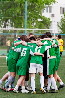 Leden van het voetbalteam omarmen na het winnen van de wedstrijd. amateurvoetbal in de open lucht. moskou, rusland.