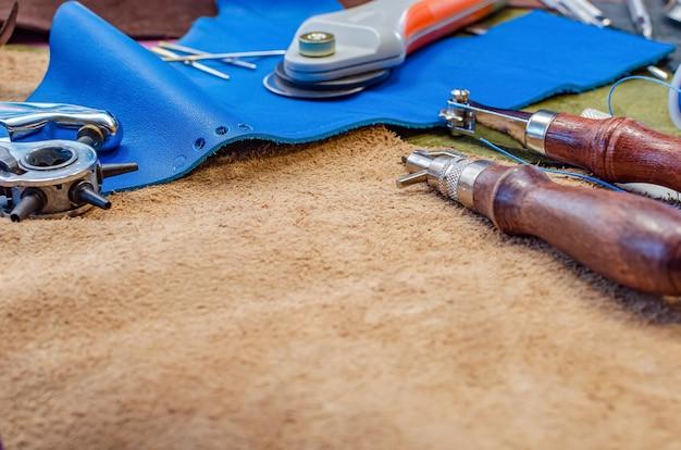 Lederen ambachtelijke tools op lederen achtergrond, plaats voor tekst, kopieer ruimte. lederen schoenmaker concept.
