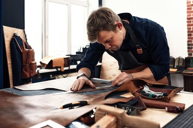 Lederen ambachtslieden werken aan het maken van measupenets in patronen aan tafel in de werkplaatsstudio.