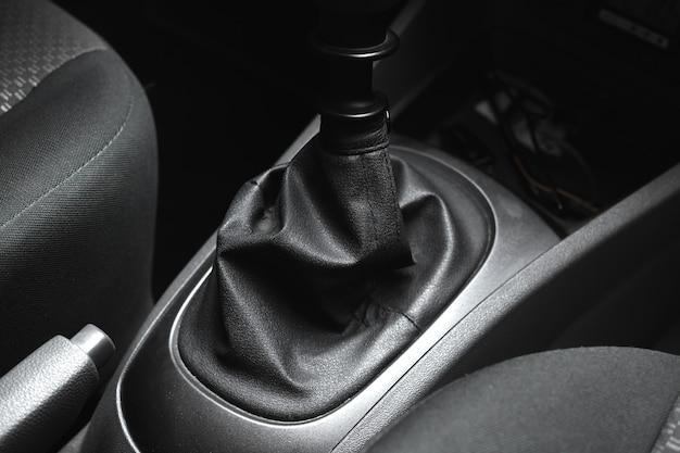 Lederen behuizing van handgeschakelde versnellingsbak in het zwarte interieur van een auto