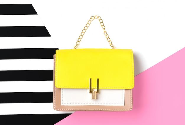 Lederen handtas geel, beige, witte kleuren op roze, witte en zwarte strepen achtergrond plat lag bovenaanzicht