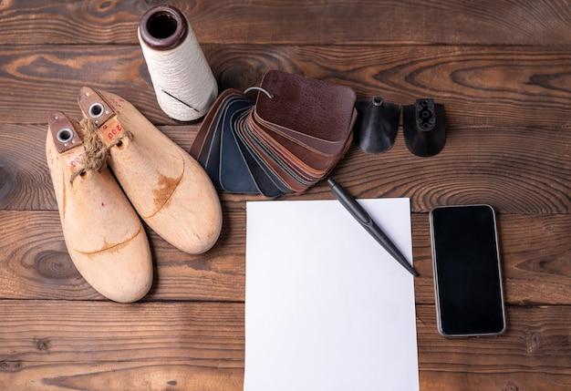 Lederen monsters voor schoenen en houten schoenleest op donkere houten tafel met leeg wit vel papier voor notities. designer meubels kleding. werkruimte schoenmaker.