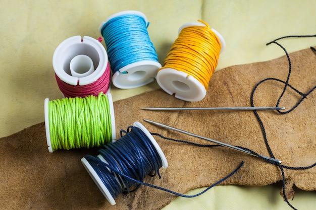 Lederen naaigereedschap op een echte lederen achtergrond.