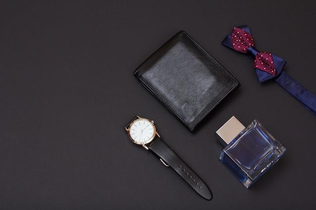 Lederen portemonnee, horloge met een zwarte leren band, keulen voor mannen en vlinderdas op zwarte achtergrond. accessoires voor heren. bovenaanzicht.