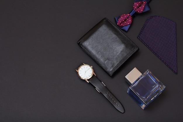 Lederen portemonnee, horloge met een zwarte leren band, keulen voor mannen, zakdoek en vlinderdas op zwarte achtergrond. accessoires voor heren. bovenaanzicht.