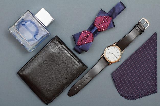 Lederen portemonnee, keulen voor mannen, vlinderdas, horloge met zwarte leren band en zakdoek op grijze achtergrond. accessoires voor heren. bovenaanzicht