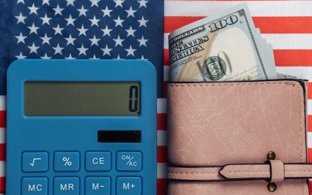 Lederen portemonnee met honderd-dollarbiljetten, rekenmachine op de vlag van de v.s.