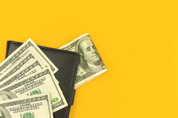 Lederen portemonnee met veel geld, concept van investering met dollarbiljetten, gele kantoortafelachtergrond, bovenaanzicht met kopieerruimtefoto