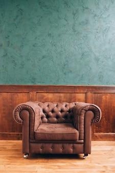 Lederen retro bank in het kantoor. leerbank op een houten achtergrond. lederen fauteuil met knopen.