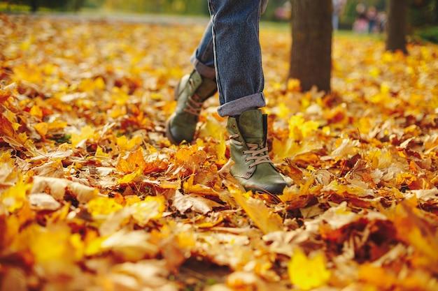 Lederen schoenen lopen op herfstbladeren buiten