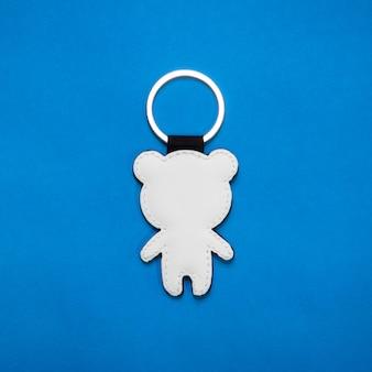 Lederen sleutelhanger in beer vorm op blauwe achtergrond papier