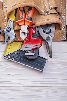 Lederen toolbelt met bouwmateriaal op houten bord bovenaanzicht