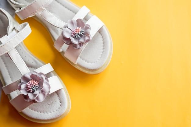 Lederen witte babymeisje zomersandalen met bloemdecoratie. babymeisjesschoenen op heldere gele achtergrond