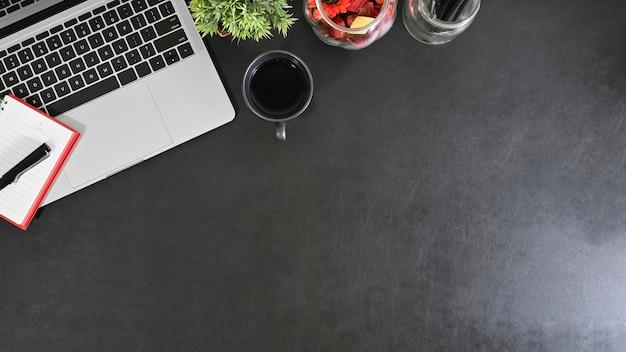 Lederen zwarte werkplek met kantoorbenodigdheden en een kopje koffie met een bureau en een kopie ruimte.
