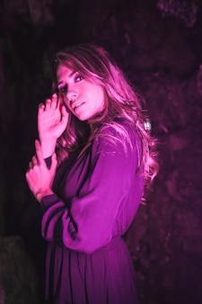 Leef een jonge blanke blonde in een zwarte jurk in een grot verlicht met roze led-licht met zacht diffuus licht aan de zijkant