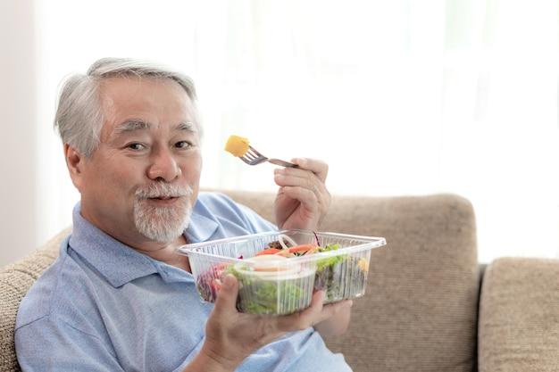 Leeft de levensstijl hogere mens gelukkig geniet van het eten van de verse salade van het dieetvoedsel op bank