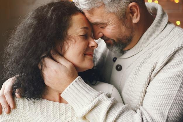 Leeftijd en mensen concept. hoger paar met giftdoos over lichtenachtergrond. vrouw in een witte gebreide trui.