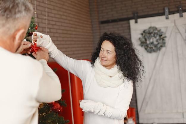 Leeftijd en mensen concept. hoger paar thuis. vrouw in een witte gebreide trui.