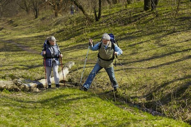 Leeftijd familie paar man en vrouw in toeristische outfit wandelen op groen gazon in zonnige dag