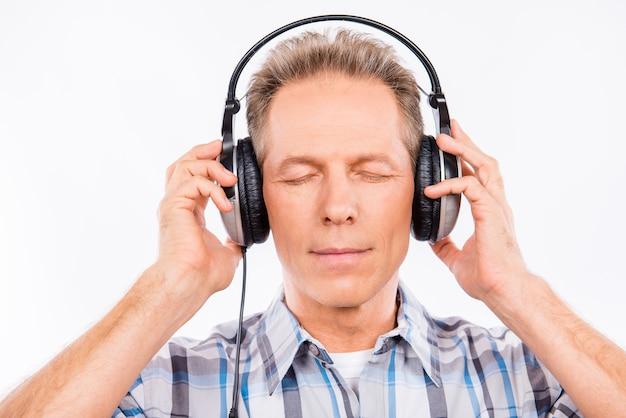 Leeftijd rustige hipster met koptelefoon luisteren naar muziek