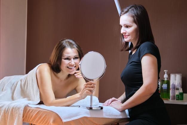 Leeftijd, schoonheid, gezicht, behandelingsconcept. vrouw van middelbare leeftijd in het kantoor van de schoonheidsspecialist, gelukkige vrouw die in de schoonheidsspiegel kijkt