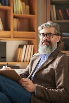 Leeftijd succesvolle psycholoog in brillen en slimme vrijetijdskleding op zoek naar jou op de achtergrond van planken met professionele literatuur