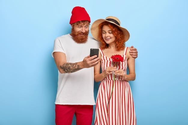 Leeftijd van smartphones. het jonge gelukkige paar bekijkt online inhoud via smartphone