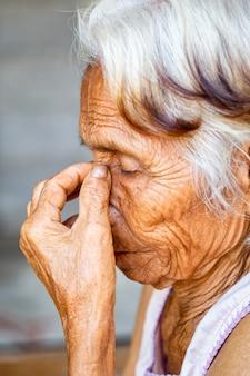 Leeftijd, visie en oud mensenconcept - sluit omhoog van hoger aziatisch vrouwengezicht en oog, aziatische hogere vrouw met sinusitis (sinusitis)