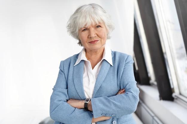 Leeftijd, volwassenheid, baan, stijl en elegantieconcept. taille-up shot van bekwame vrouwelijke baas van in de zestig poseren bij het raam op haar kantoor, armen gekruist, kijken met een serieuze zelfverzekerde glimlach