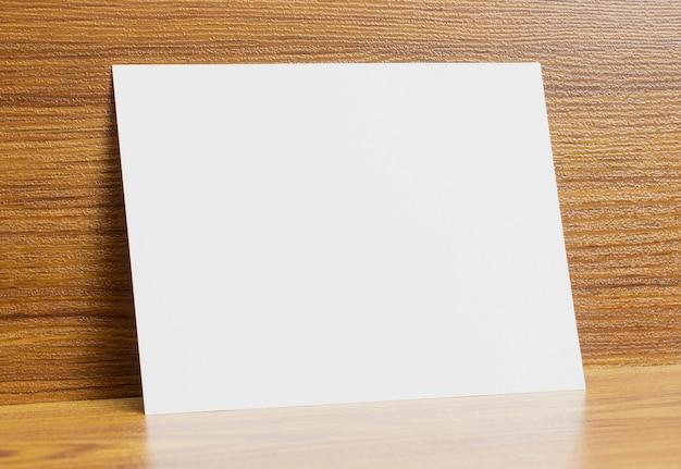 Leeg a6-document kader dat op houten geweven bureau wordt gesloten